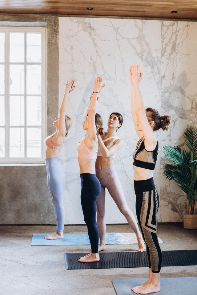 Mujeres realizando la postura de brazos estirados en el saludo al sol