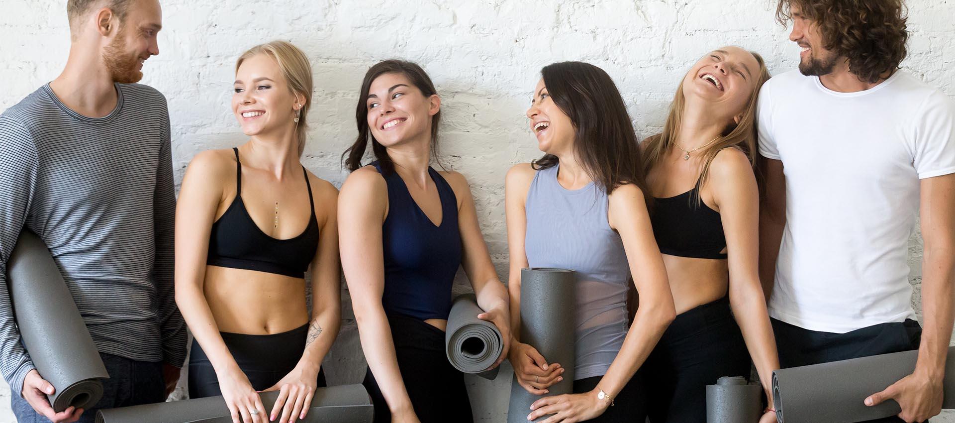 personas jóvenes antes de practicar las posturas de yoga en una clase